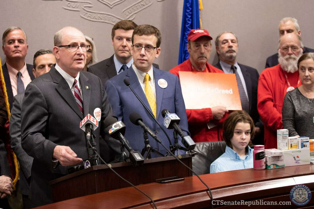 State lawmakers Sen. Kevin Kelly, Rep. Sean Scanlon and Sen. Matt Lesser join with advocates and members of AARP on Feb. 13 in Hartford to share Insurance Committee plans to cap insulin copays.