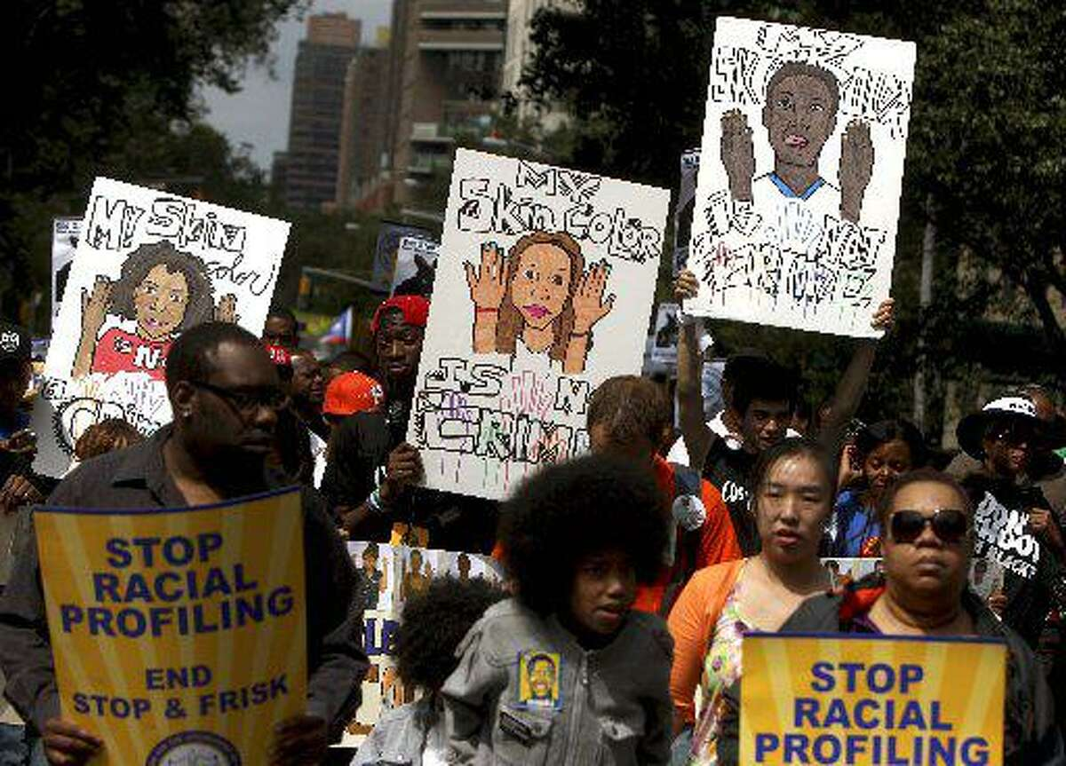"""In this June 17, 2012 file photo, demonstrators hold signs during a silent march in New York to end the New York City Police Department's """"stop-and-frisk"""" program. A federal trial is scheduled to begin in New York on Monday, March 18, 2013, where the NYPD's practice of stopping, questioning and frisking people on the street will face a sweeping legal challenge."""