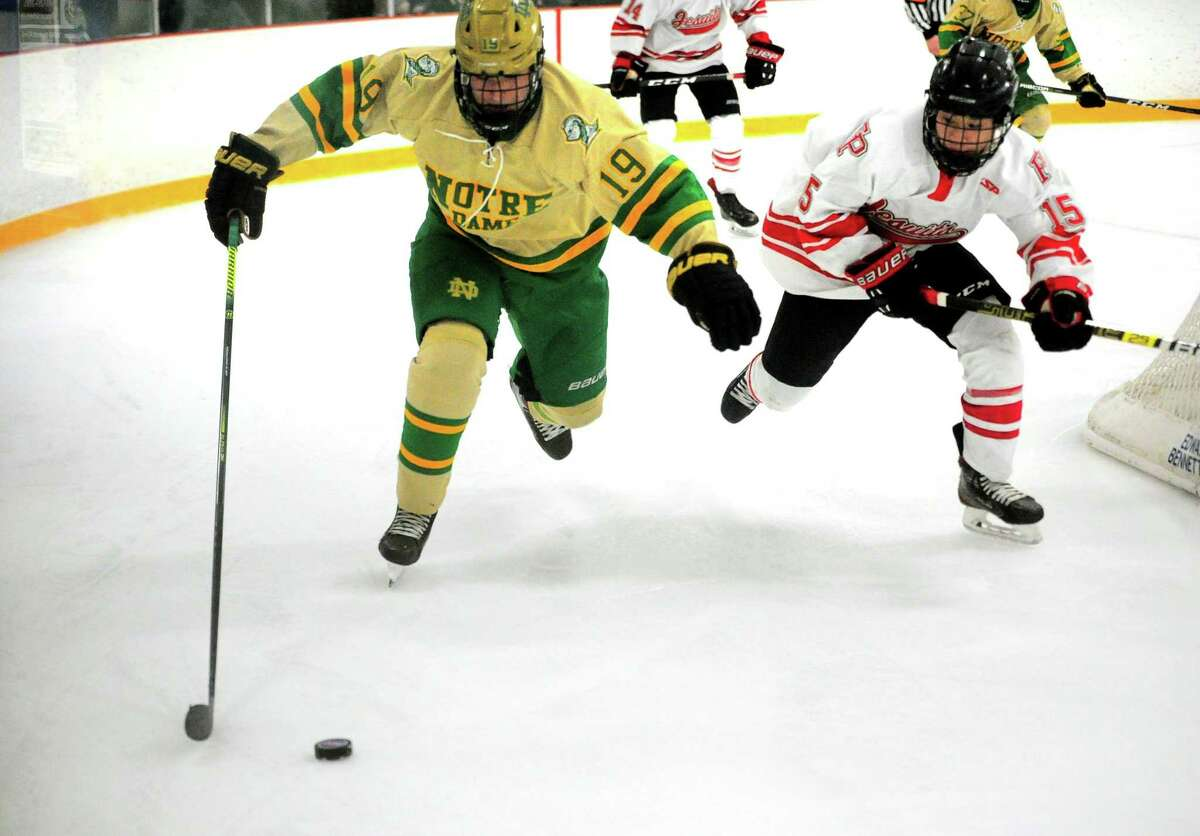 Notre Dame of West Haven's Robert Allan (19) and Fairfield Prep's Aaron Wong (15) chase down the puck during SCC Div. I hockey championship in West Haven, Conn., on Friday Mar. 6, 2020.