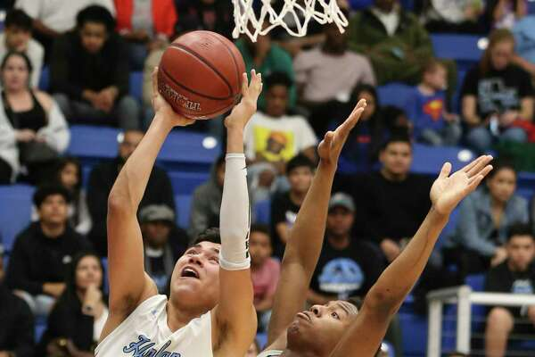 Harlan's Elijah Lomas (32) scores against Sharyland Pioneer's Lavar Lindo (right) during their Boys 5A Regional semifinal basketball game on Friday, Mar. 6, 2020.