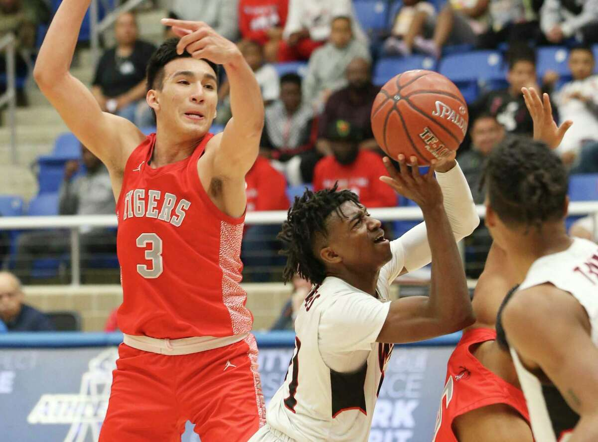 Wagner's JaSean Jackson (right) speeds past Laredo Martin's Kevin Garcia (03) during their Boys 5A Regional semifinal basketball game on Friday, Mar. 6, 2020. Wagner defeated Laredo Martin, 58-47, to advance to the regional final game.