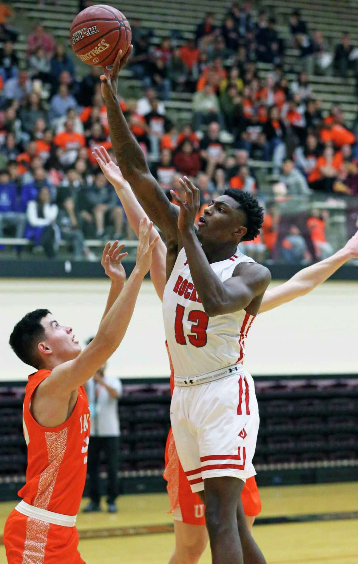 Rocket forward Davion Wilson tips back an inbounds pass to teammate MIke Chandler for an open layiup as Judson plays United in Class 5A regional semifinal basketball at Littleton Gym on Feb. 6, 2020.