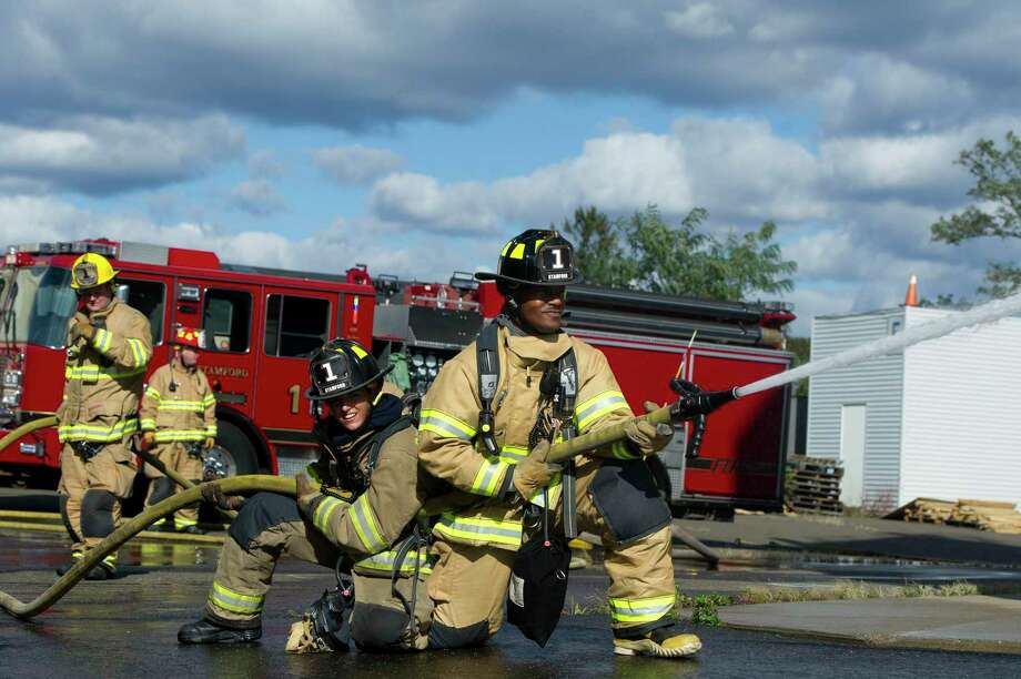 In this file photo from Oct. 24, 2018, Stamford firefighters spray water from a hose while training at the Fire Department Drill Field on Magee Ave. in Stamford, Conn. Photo: Michael Cummo / Hearst Connecticut Media / Stamford Advocate