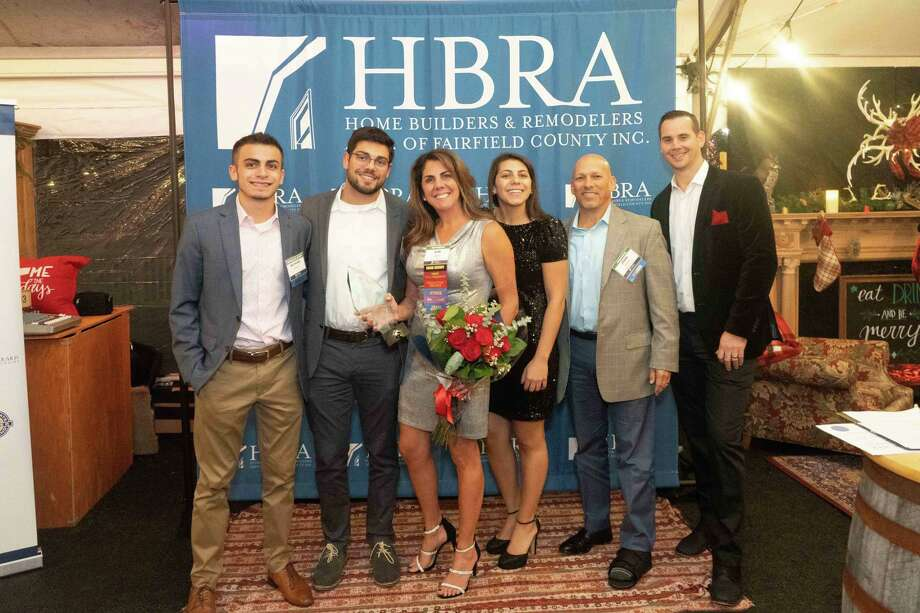 Kim DiMatteo of Bethany, center, branch manager at DiMatteo Insurance of Shelton, recently received the John P. Rowins Meritorious Service Award from the Home Builders and Remodelers Association (HBRA) of Fairfield County and was congratulated by Anthony DeRosa, far right, HBRA President and owner of DeRosa Builders. She is also pictured with her sons, Michael and Anthony DiMatteo, at her left, her daughter, Jessica DiMatteo, at her right, and her husband, John DiMatteo of DiMatteo Financial Services, second from her right, at the Association's Annual Awards Dinner. Photo: Contributed Photo / Connecticut Post