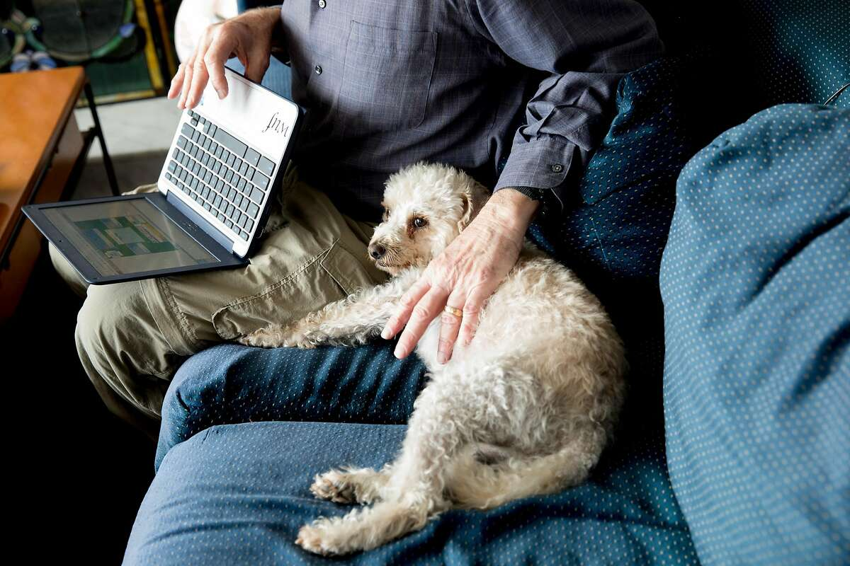 Eric Ratner plays Bridge on his computer while sitting with his dog Gnar he shares with his wife in Pacifica, Calif. Saturday, March 7, 2020. Ratner and his wife have decided they will be staying home as much as possible now that the virus is out there. Those with high risk of serious illness from the coronavirus are choosing to avoid social interactions for fear of getting sick, now that the virus appears to be circulating in the community.