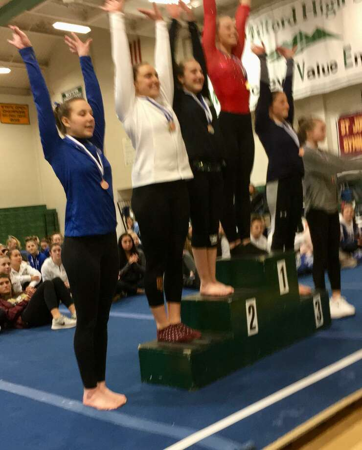 The top six finishers on uneven bars acknowledge the cheers, led by winner Alexa Granfield of Tolland (center, red), at the gymnastics State Open Saturday in New Milford. Photo: Staff Photo
