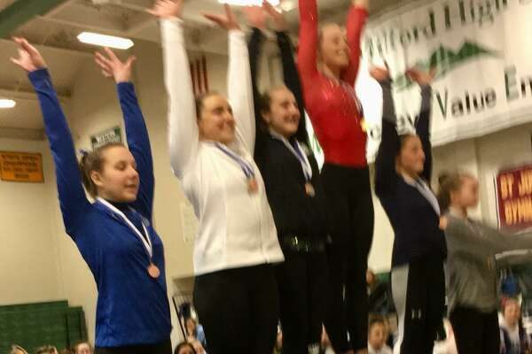 The top six finishers on uneven bars acknowledge the cheers, led by winner Alexa Granfield of Tolland (center, red), at the gymnastics State Open Saturday in New Milford.