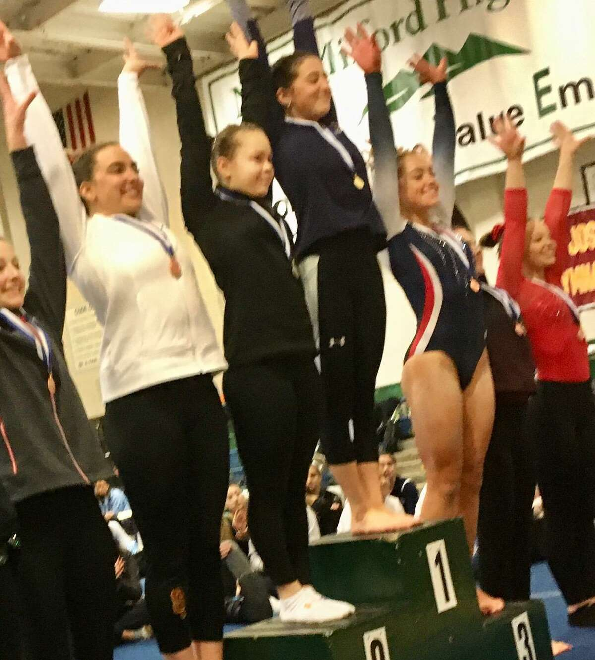 The top six finishers in the all-around, led by Jenna Davidson of Woodstock Academy (center, blue), acknowledge the crowd at the gymnastics State Open on Saturday in New Milford.