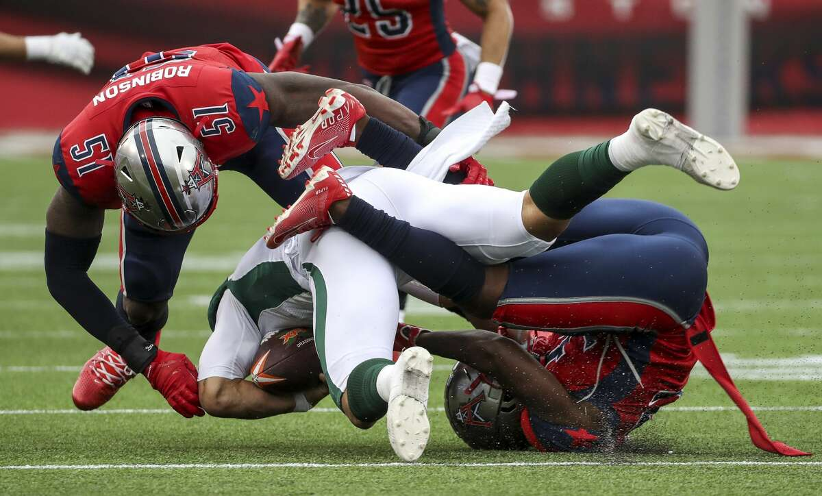 Seattle Dragons quarterback B.J. Daniels (7) is tackled by Houston Roughnecks cornerback Deatrick Nichols (32) and linebacker Edmond Robinson (51) during the third quarter of an XFL game on Saturday, March 7, 2020, at TDECU Stadium in Houston.