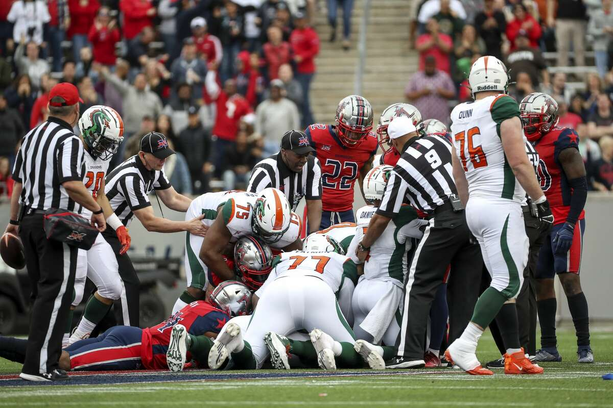 Houston Roughnecks and Seattle Dragons players go after a fumble during the fourth quarter of an XFL game on Saturday, March 7, 2020, at TDECU Stadium in Houston.
