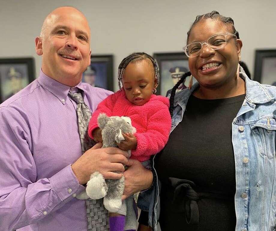 From left to right: Detective Michael Harton with 1-year-old Eimann and her mother, Nicole Brown-Buchanan. Photo: Contributed Photo / North Haven Police Department
