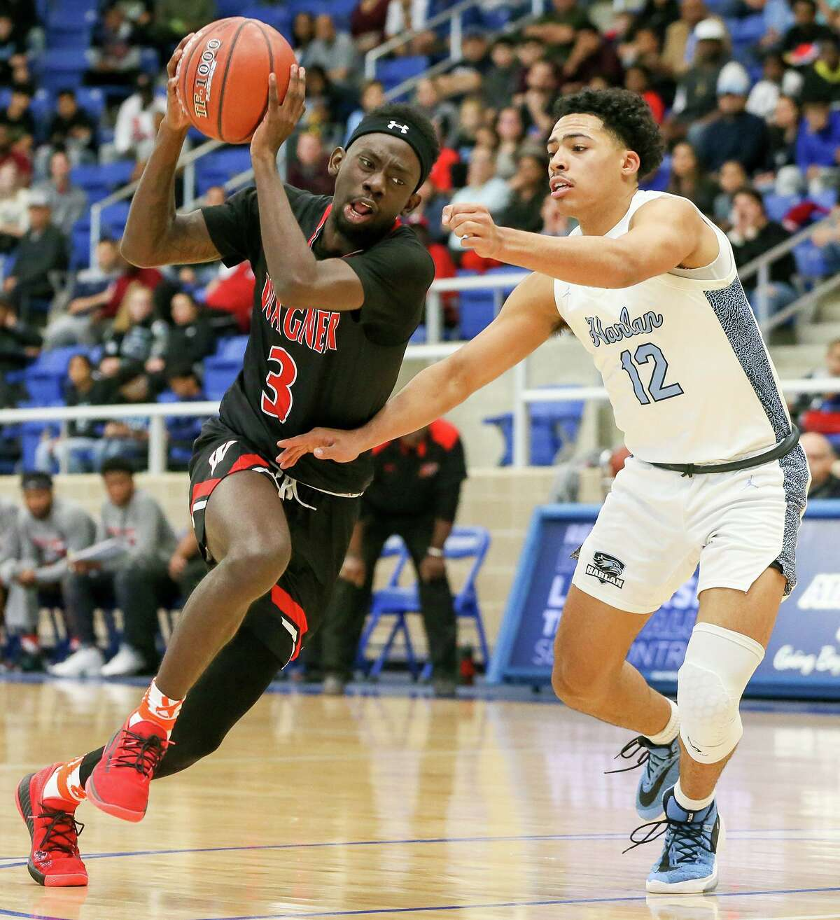 Wagner's Braelon Seals, left, drives on Harlan's Zarion Pitre in the first half of their Class 5A Regional final game at Northside Gym on Saturday, March 7, 2020. Wagner advanced to the state tournament with a 64-48 victory over Harlan.