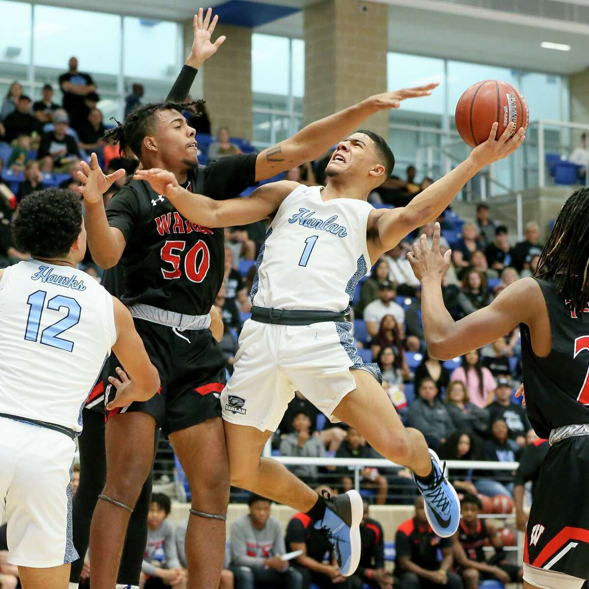 Wagner's Joshua Cobbs (50) tries to block a shot by Harlan's Jalen Mangum (1) in the first half of their Class 5A Regional final game at Northside Gym on Saturday, March 7, 2020. Wagner advanced to the state tournament with a 64-48 victory over Harlan.