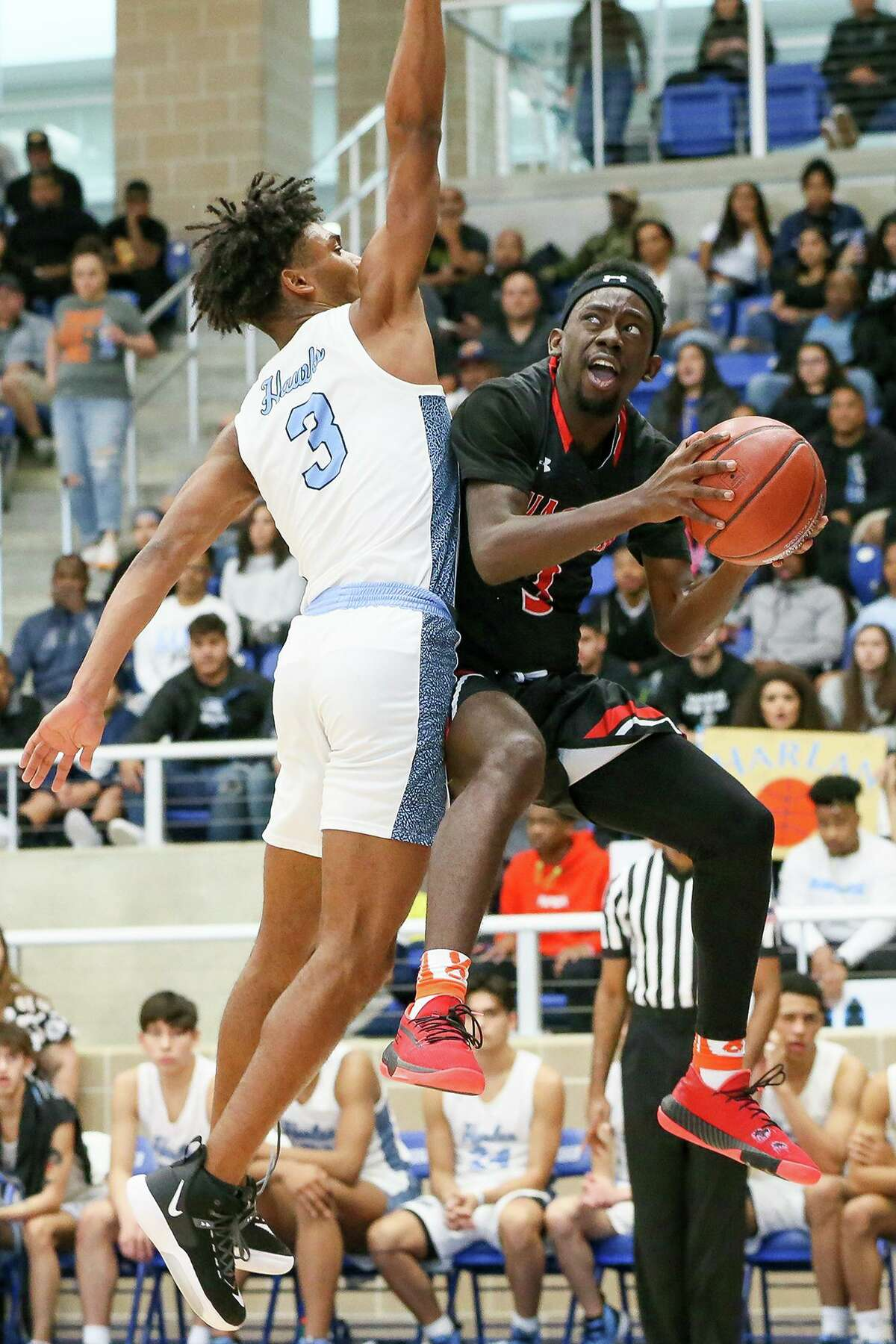 Wagner's Braelon Seals, right, looks to the basket as Harlan's Dre Spriggs defends in the first half of their Class 5A regional final game at Northside Gym on March 7, 2020.