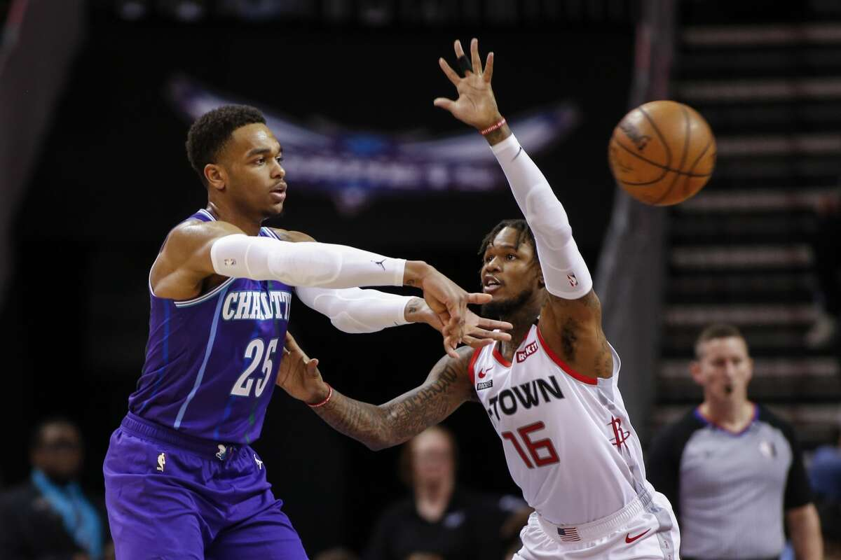 Charlotte Hornets forward P.J. Washington, left, passes the ball around Houston Rockets guard Ben McLemore during the second half of an NBA basketball game in Charlotte, N.C., Saturday, March 7, 2020. (AP Photo/Nell Redmond)