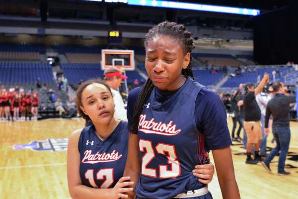 Veterans Memorial players Daelah Edwards and Sahara Jones react and walk off the court following their loss to Frisco Liberty in the UIL 5A Finals Saturday afternoon at the Alamodome.