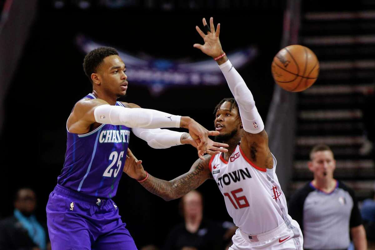 Hornets forward P.J. Washington, left, passes the ball around Rockets guard Ben McLemore during the second half of Saturday's game in Charlotte, N.C.