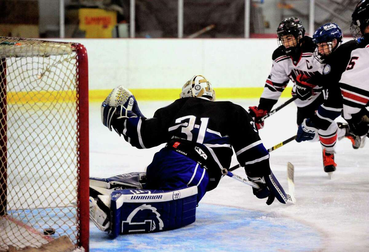 New Canaan's Justin Wietfeldt (17), in back at right, sends the puck pas Darien goalie Chris Schofield to score during FCIAC boys hockey championship action in Greenwich, Conn., on Saturday Mar. 7, 2020.
