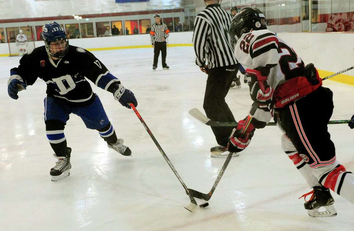 Darien's Jamison Moore (17), left, tries to disrupt New Canaan's Richard Carter Spain (22) as he moves the puck during FCIAC boys hockey championship action in Greenwich, Conn., on Saturday Mar. 7, 2020.