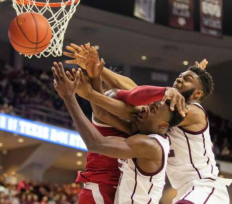 Texas A&M's Emanuel Miller, left, and Josh Nebo vie with Arkansas' Adrio Bailey for the ball on Saturday.