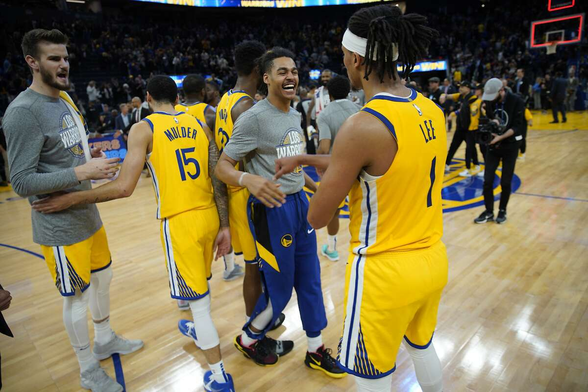 Golden State Warriors guard Jordan Poole (center) and Warriors guard Damion Lee (right) following the fourth quarter of an NBA game against the Philadelphia 76ers at Chase Center on Saturday, March 7, 2020, in San Francisco, Calif. The Warriors won 118-114.