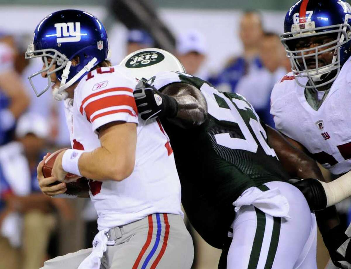 New York Giants quarterback Eli Manning escapes a tackle attempt by New York Jets' Shaun Ellis, center, as Giants' Kareem McKenzie, right, tries to help Manning during the second quarter of a preseason NFL football game at New Meadowlands Stadium in East Rutherford, N.J., Monday, Aug. 16, 2010. (AP Photo/Bill Kostroun)