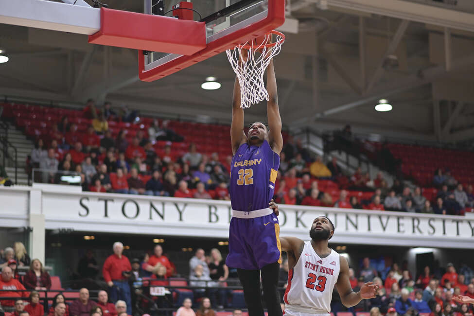 UAlbany's Romani Hansen (32) dunks against Stony Brook's Andrew Garcia (23) in Saturday's America East Conference quarterfinal game on Long Island.