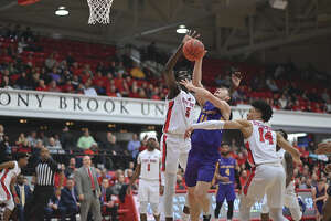 UAlbany's Cameron Healy (11) drives to the basket against Stony Brook's Mouhamadou Gueye (5) and Tyler Stephenson (14) in the America East Conference quarterfinals on Saturday, March 8 2020.