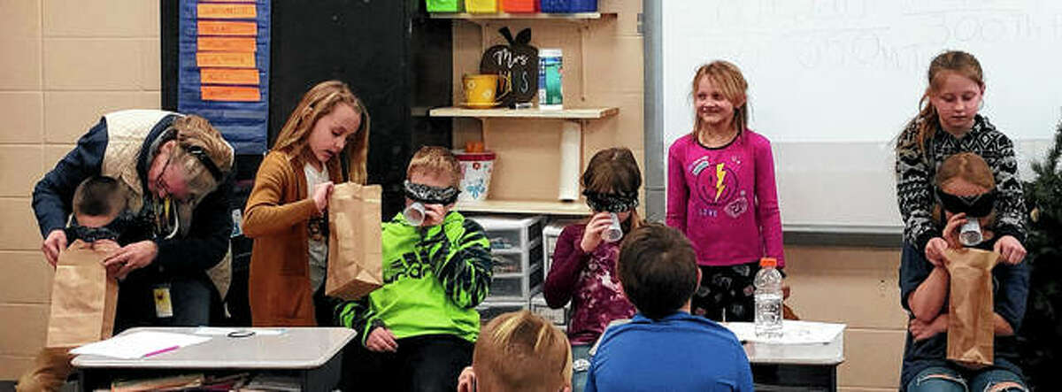 The Pike-Scott Agriculture in the Classroom program recently visited Pleasant Hill Elementary School to teach its third-graders about pigs. Students in Mrs. Evans' class played a game to demonstrate how swine use their sense of smell to find food underground. Students participating include Easton Hansen (front row, from left, blindfolded), Tyn Burdick, Emma Jones and Elli Hurst; helper Mrs. Arnold (back row, from left), Mylee Niehaus, Jaici Yanczer and Bella Douglas.