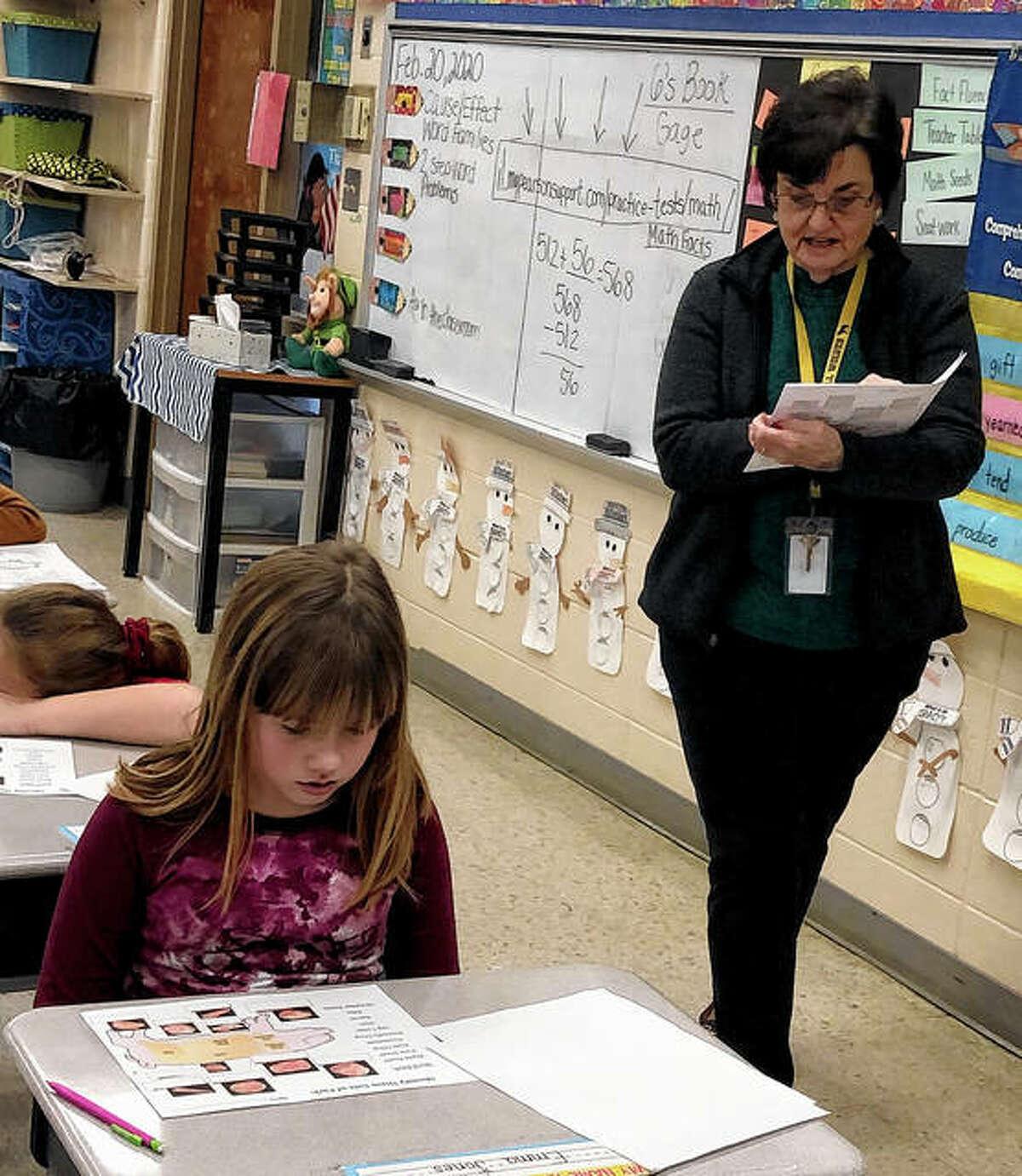 Volunteer Sharon Van Dyne (right) helps student Emma Jones with her worksheet on pork cutlets.