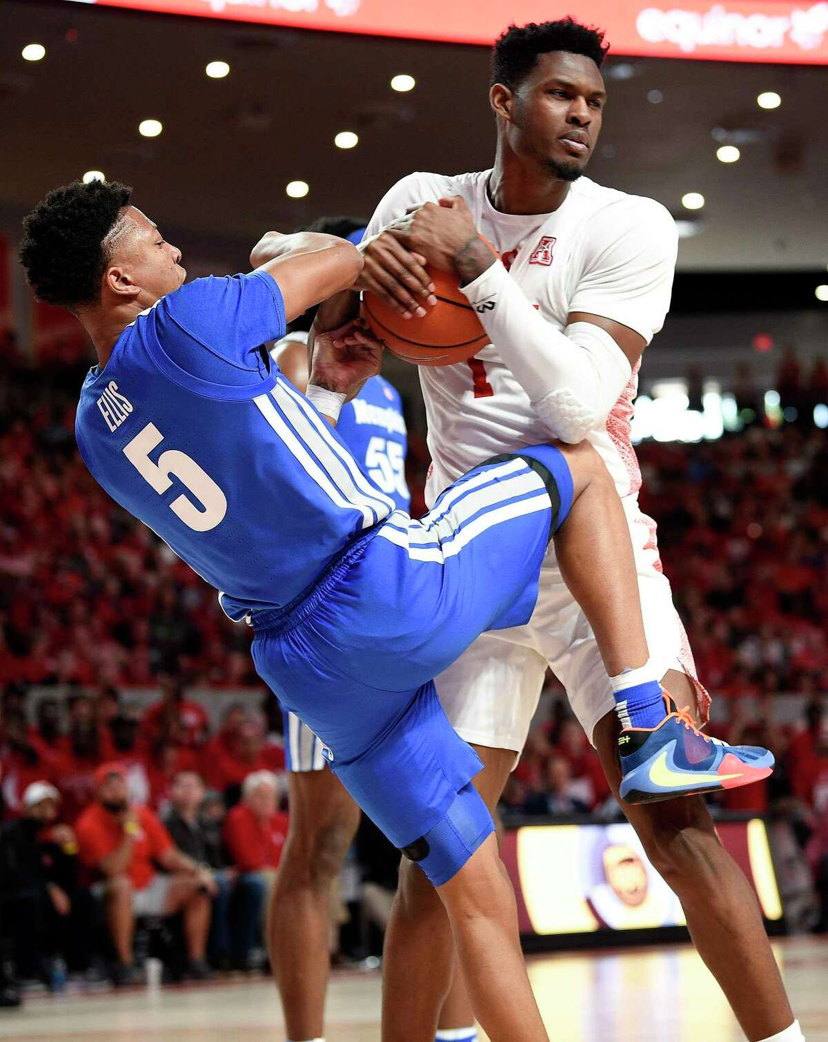 Houston center Chris Harris Jr., right, rips the ball away from Memphis guard Boogie Ellis during the first half of an NCAA college basketball game, Sunday, March 8, 2020, in Houston.
