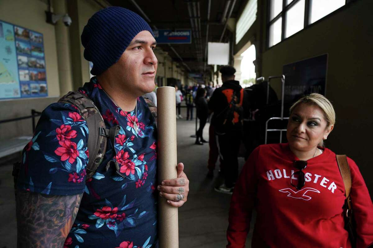 Passengers of Carnival Cruise and newlywed couple Theodore Herrera, 39, left and Liza Herrera, 40, right, who just got married on the ship, talk about their last-minute nuptial changes after arriving at Port of Galveston Cruise Terminal on Sunday March 8, 2020 in Galveston, Texas. The cruise ship was rerouted over worries it wouldn't be able to dock in some Caribbean ports because many destinations are tightening entry policies amid growing global concern over the COVID-19 outbreak.