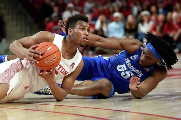 Houston forward Fabian White Jr., left, picks ups. Loose ball from Memphis forward Precious Achiuwa during the second half of an NCAA college basketball game, Sunday, March 8, 2020, in Houston.