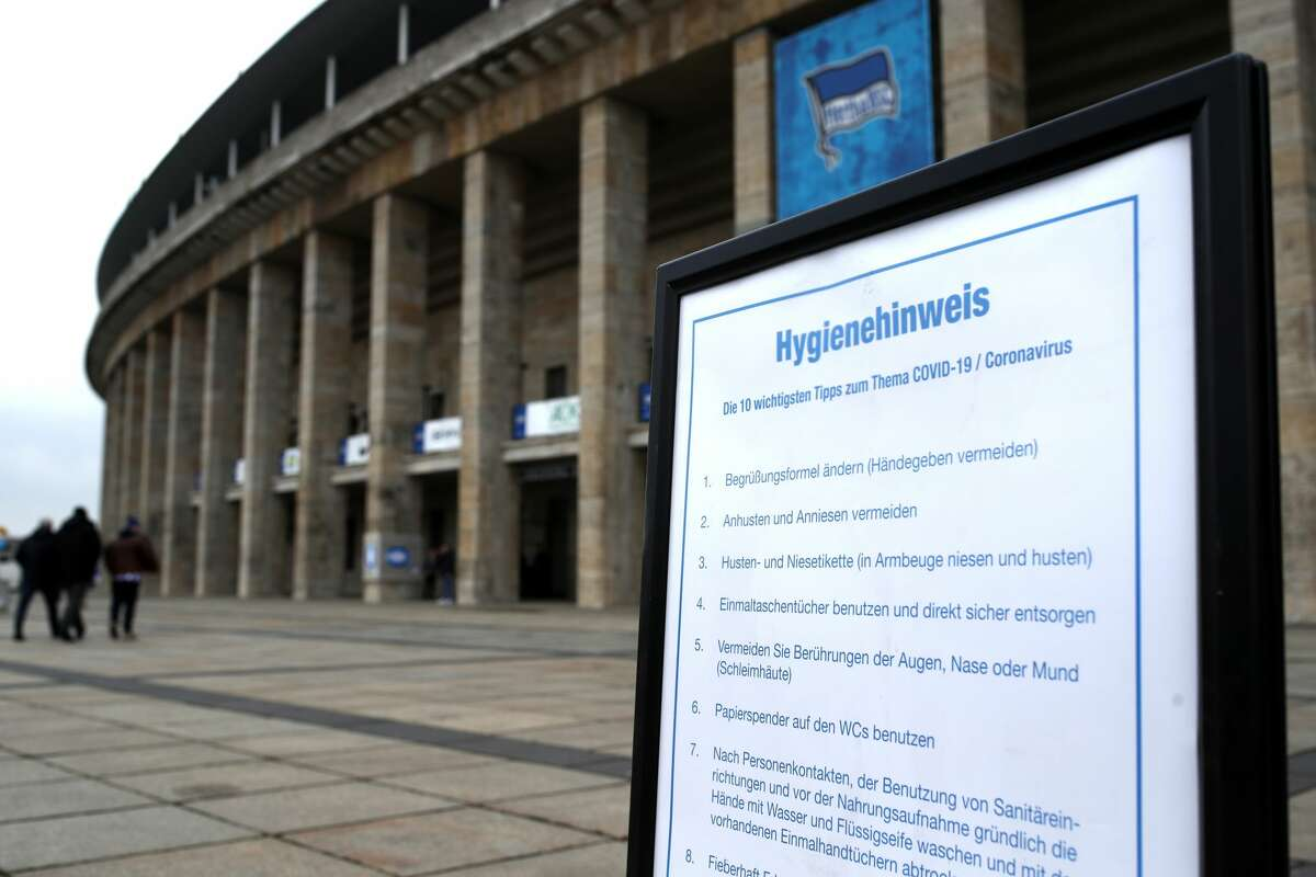 BERLIN, GERMANY - MARCH 07: A sign about Coronavirus is handed out prior to the Bundesliga match between Hertha BSC and SV Werder Bremen at Olympiastadion on March 07, 2020 in Berlin, Germany. (Photo by Maja Hitij/Bongarts/Getty Images)