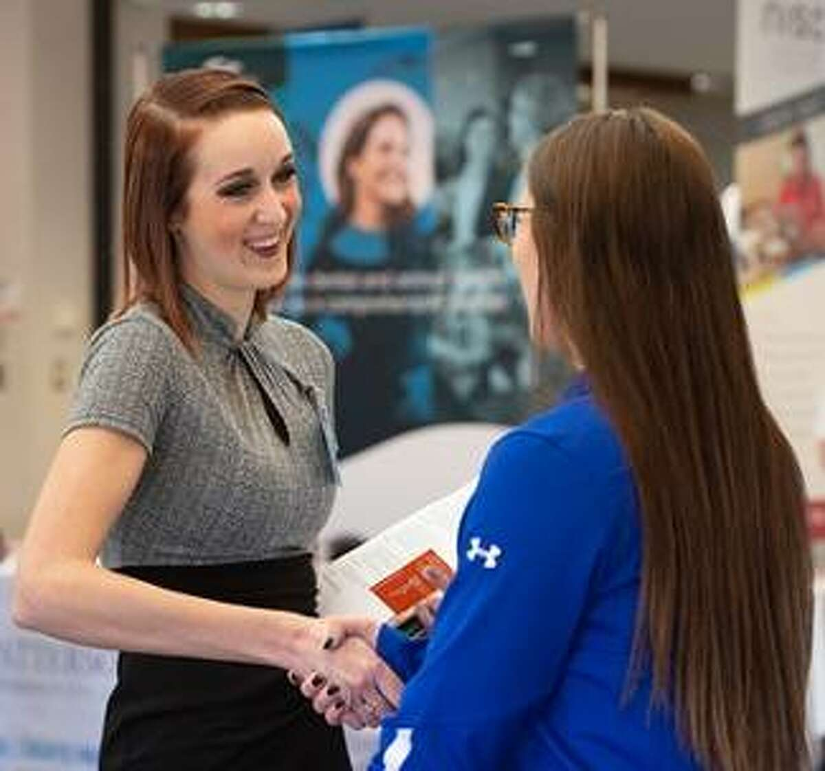 SIUE MBA student Taylor Gresens greets Sarah Peters with Brooksource during the Spring Career Fair.