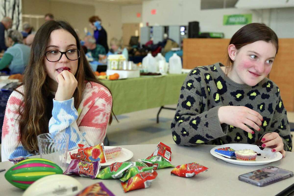 Trying out some treats are Sarah Albanese, 12, of Wilton, left, and Juliette Axen, 12, of Ridgefield, at the Congregation of Humanistic Judaism's Purim celebration at Bedford Middle School on March 8, 2020, in Westport.