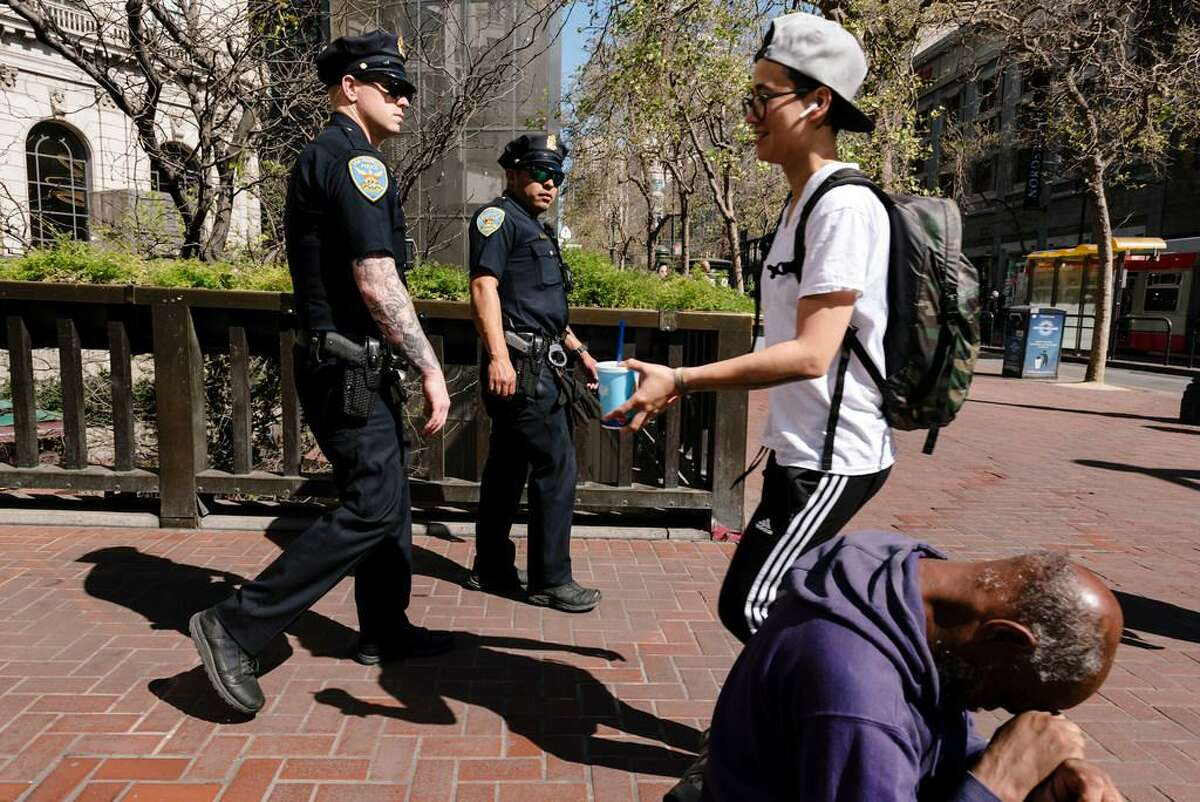 San Francisco Police Officers Cory McDowell, left, and Nick Parkin walk their beat near the Powell Street BART station plaza in San Francisco, California, on Wednesday, March 4, 2020.