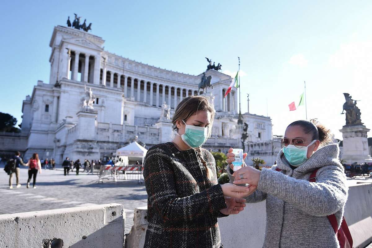 Women wearing face mask disinfect their hands in central Piazza Venezia, in Rome, Sunday, March 8, 2020. Italy announced a sweeping quarantine early Sunday for its northern regions, igniting travel chaos as it restricted the movements of a quarter of its population in a bid to halt the new coronavirus' relentless march across Europe. (Alfredo Falcone/LaPresse via AP)