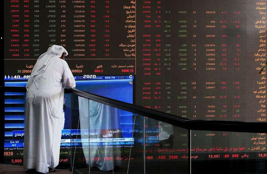 A Kuwaiti trader checks stock prices at Boursa Kuwait in Kuwait City, on March 8, 2020. Photo: Yasser Al-zayyat, AFP Via Getty Images