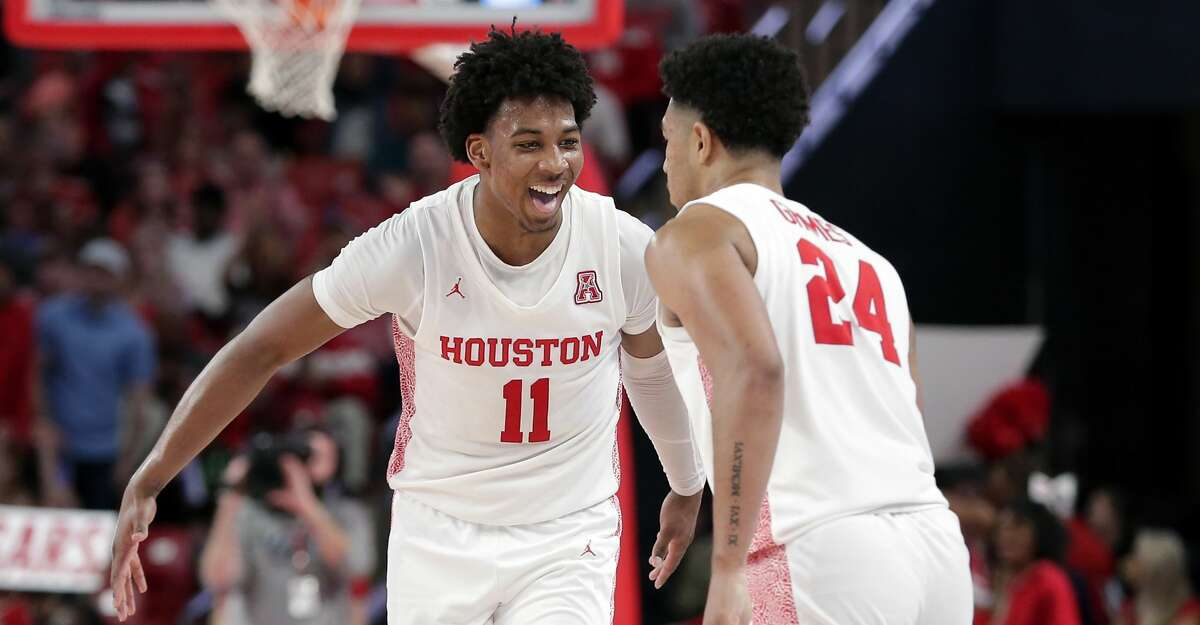 Houston guards Nate Hinton (11) and Quentin Grimes (24) celebrate a score by Grimes against Memphis during the second half of an NCAA college basketball game Sunday, March 8, 2020, in Houston. (AP Photo/Michael Wyke)