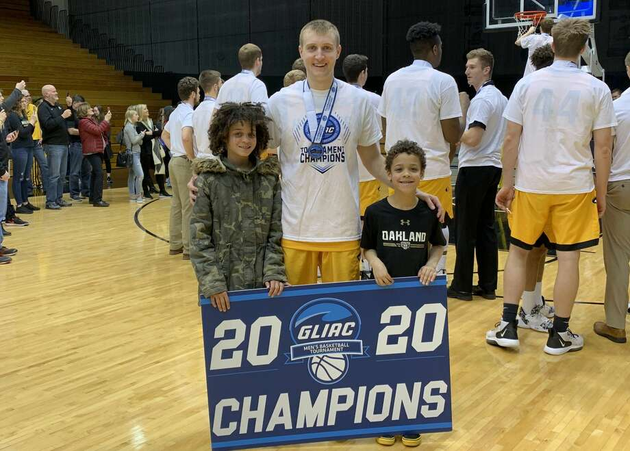 Michigan Tech's Carter Johnston, a former Beaverton standout, poses with his cousins Layla Stewart and Andre Stewart after the Huskies defeated Northwood in Sunday's GLIAC Tournament final at Grand Valley State. Photo: Photo Provided