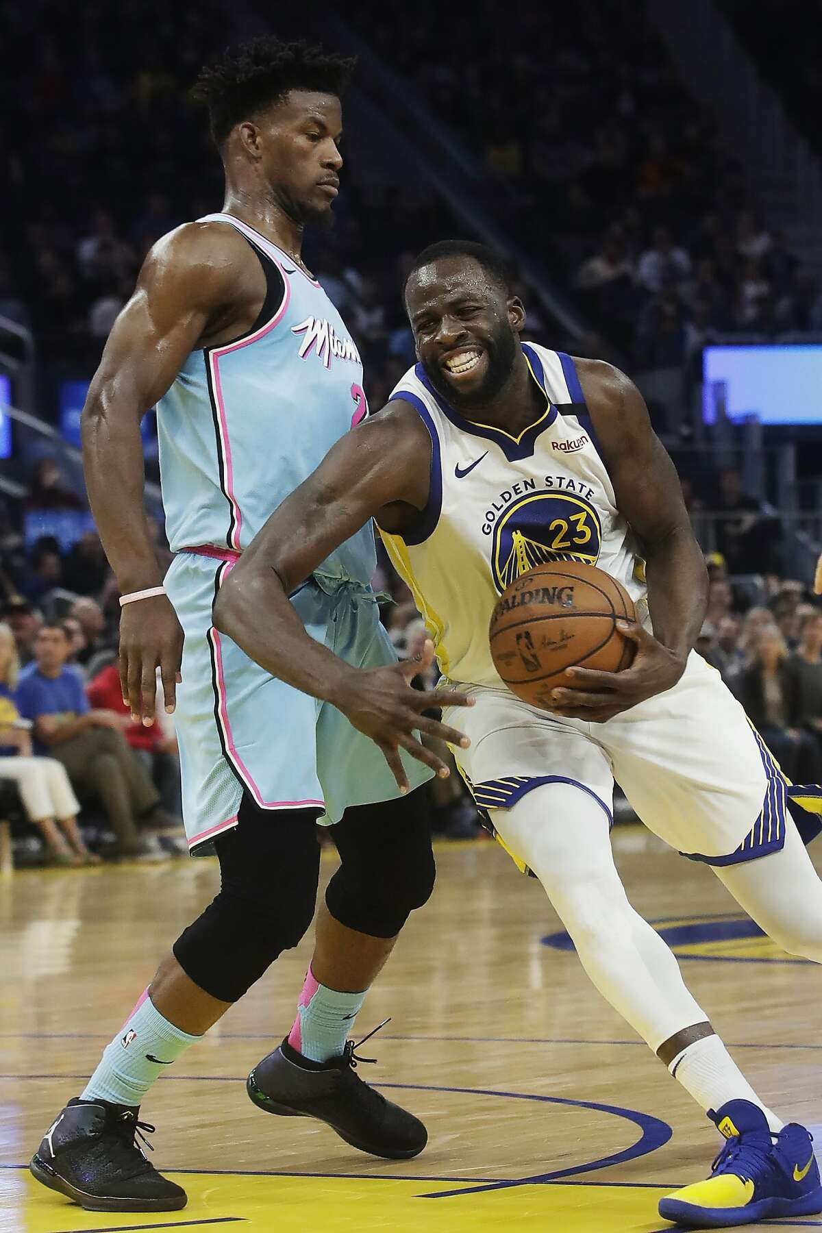 Golden State Warriors forward Draymond Green, right, drives against Miami Heat forward Jimmy Butler during the second half of an NBA basketball game in San Francisco, Monday, Feb. 10, 2020. (AP Photo/Jeff Chiu)