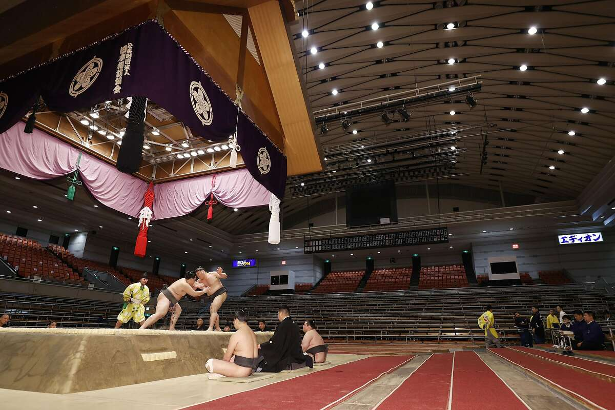 Sumo wrestlers fight on the ring as spectators' seats are empty during the Spring Grand Sumo Tournament in Osaka, western Japan, Sunday, March 8, 2020. The 15-day sumo tournament started on Sunday with no spectators, affected by fears of the new coronavirus outbreak. (Kyodo News via AP)