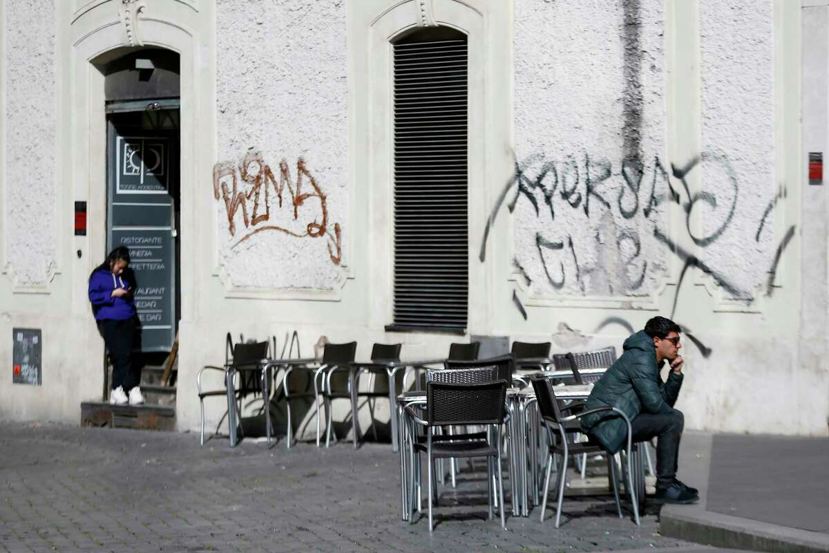 A man sits at a table as others are empty at a cafe in Largo Argentina square amid growing concern about the spread of a new coronavirus in Rome Saturday, March 7, 2020. Italy is taking an almighty hit to its already weak economy from being the focal point of the coronavirus emergency in Europe. (Cecilia Fabiano/LaPresse via AP)
