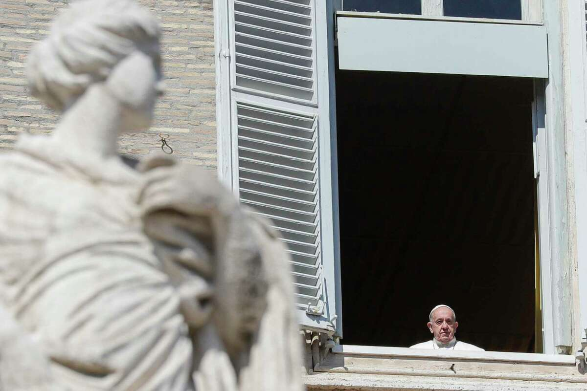 Pope Francis stands briefly at his window overlooking St. Peter's Square after delivering the Angelus prayer on a giant screen in St. Peter's Square aimed at discouraging crowds, at the Vatican, Sunday, March 8, 2020. The pope in his streamed remarks said he was close in prayers to those suffering from the virus and to those caring for them. (AP Photo/Andrew Medichini)