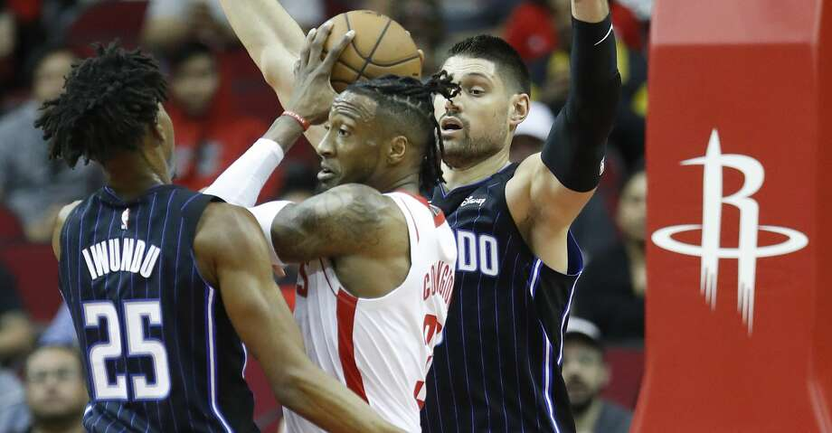 Houston Rockets forward Robert Covington (33) is defended by Orlando Magic center Nikola Vucevic (9) and forward Wes Iwundu (25) during the first half of an NBA basketball game, in Houston,Sunday, March 8, 2020. Photo: Karen Warren/Staff Photographer