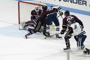 Union defenseman Joseph Campolieto ties up Yale's Luke Stevens.