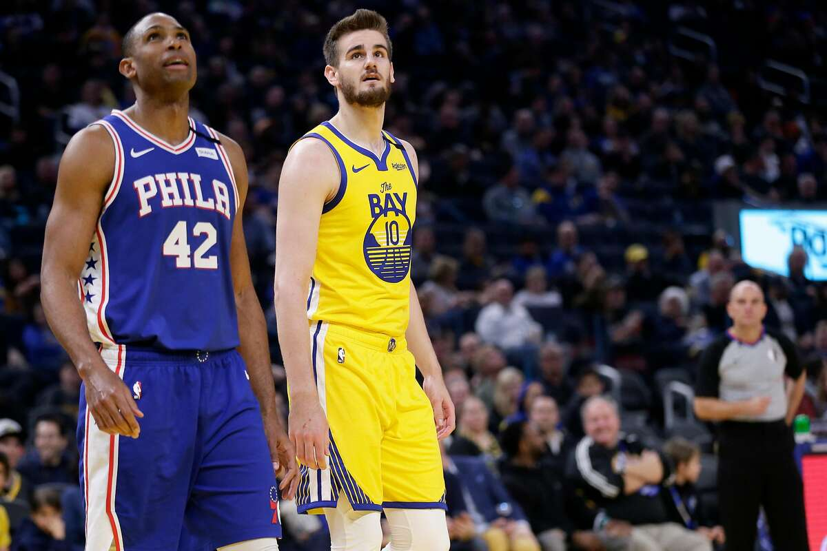 Golden State Warriors forward Dragan Bender (10) and Philadelphia 76ers forward Al Horford (42) watch a Warriors free throw in an NBA game at Chase Center on Saturday, March 7, 2020, in San Francisco, Calif.