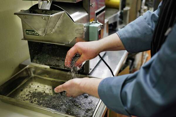 Joe Schulte, Executive chef at Toro Cantina, checks the ground blue corn coming out of a stone grinder on Thursday, March 5, 2020, in Albany, N.Y. The blue corn once ground up will be used to make tortillas. (Paul Buckowski/Times Union)