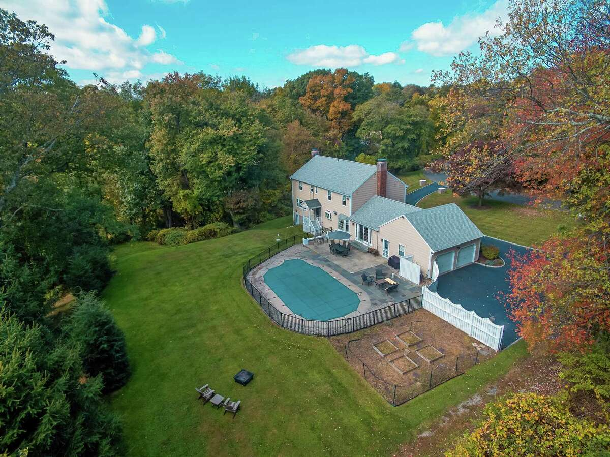 This 1.03-acre level and sloping property features a heated in-ground swimming pool, patio, professional landscaping, and vegetable gardens.